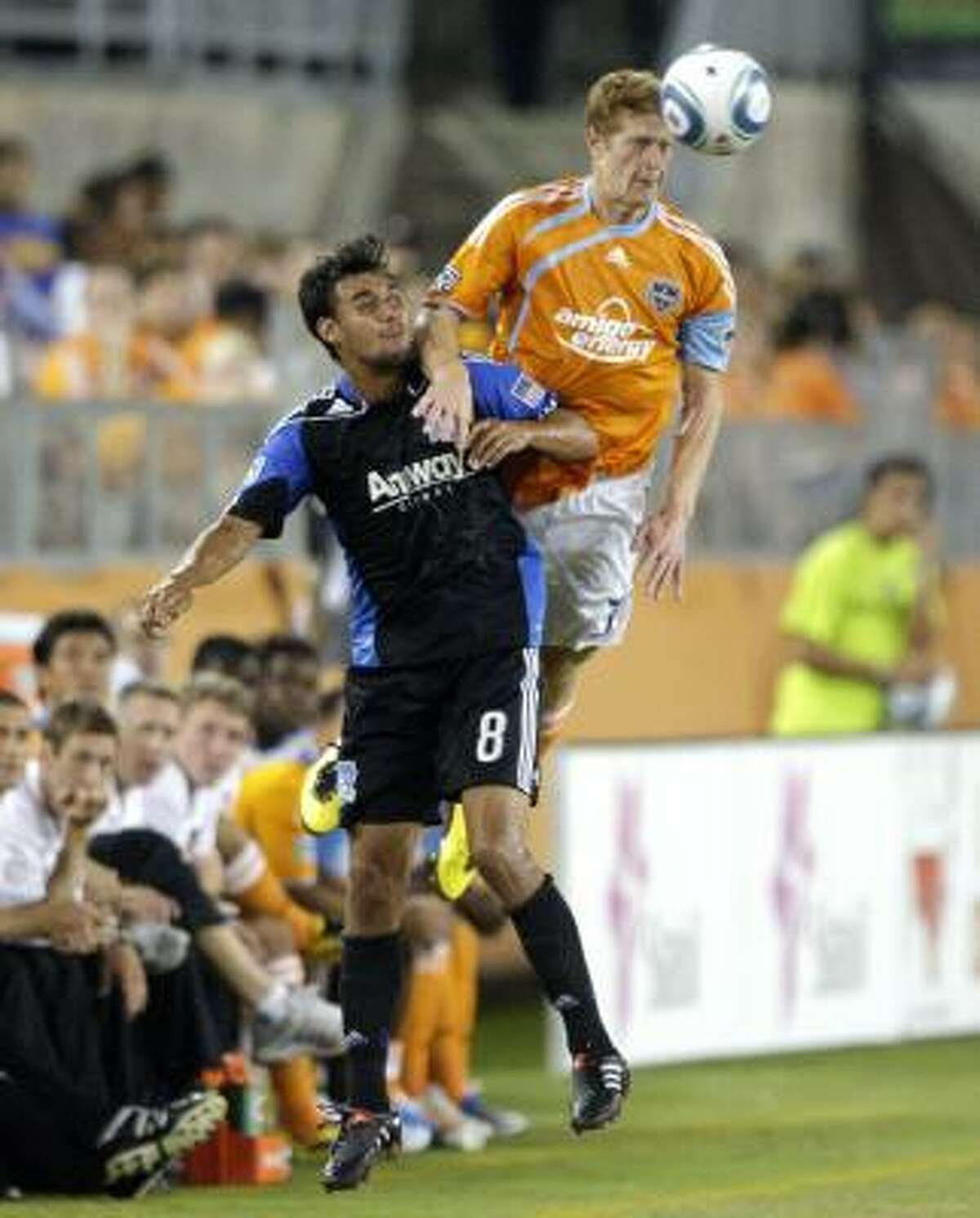 The Dynamo's Andrew Hainult goes over the top of Chris Wondolowski for a header.