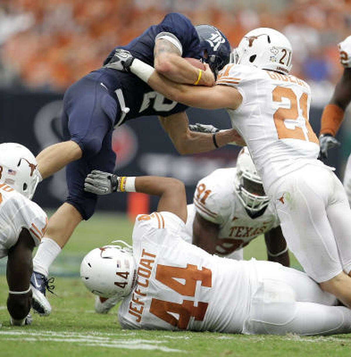 Rice running back Sam McGuffie (2) is hit hard by Texas safety Blake Gideon (21) as he tries to jump over a pile of players.