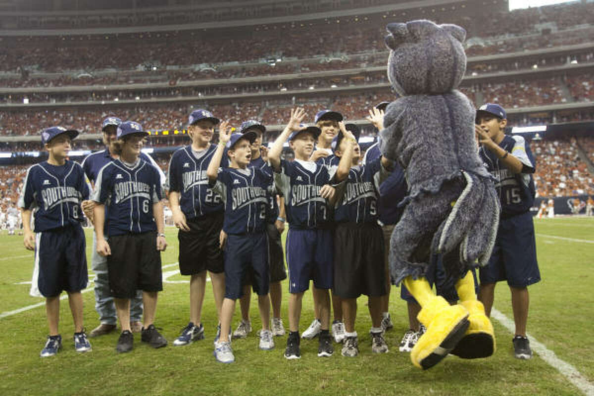 Rice mascot Sammie the Owl high fives the Pearland All-Stars baseball team as they are recognized on the field during the fourth quarter.