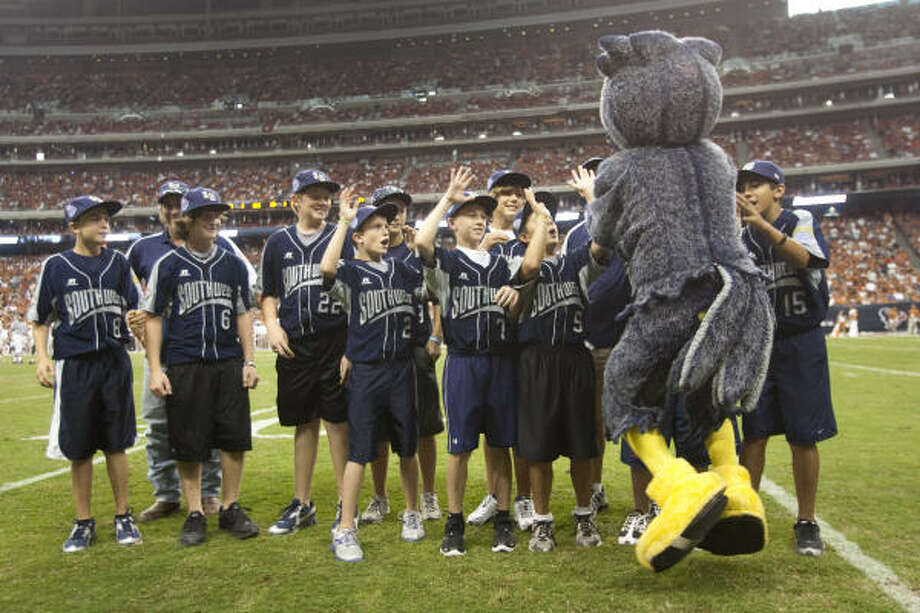 Rice mascot Sammie the Owl high fives the Pearland All-Stars baseball team as they are recognized on the field during the fourth quarter. Photo: Brett Coomer, Chronicle