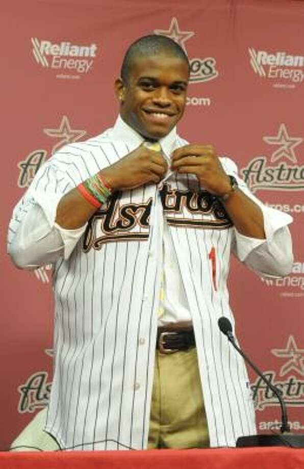 Delino DeShields Jr., the Astros' top draft pick, tries on a uniform during the news conference to announce his signing. Photo: Julio Cortez, Chronicle