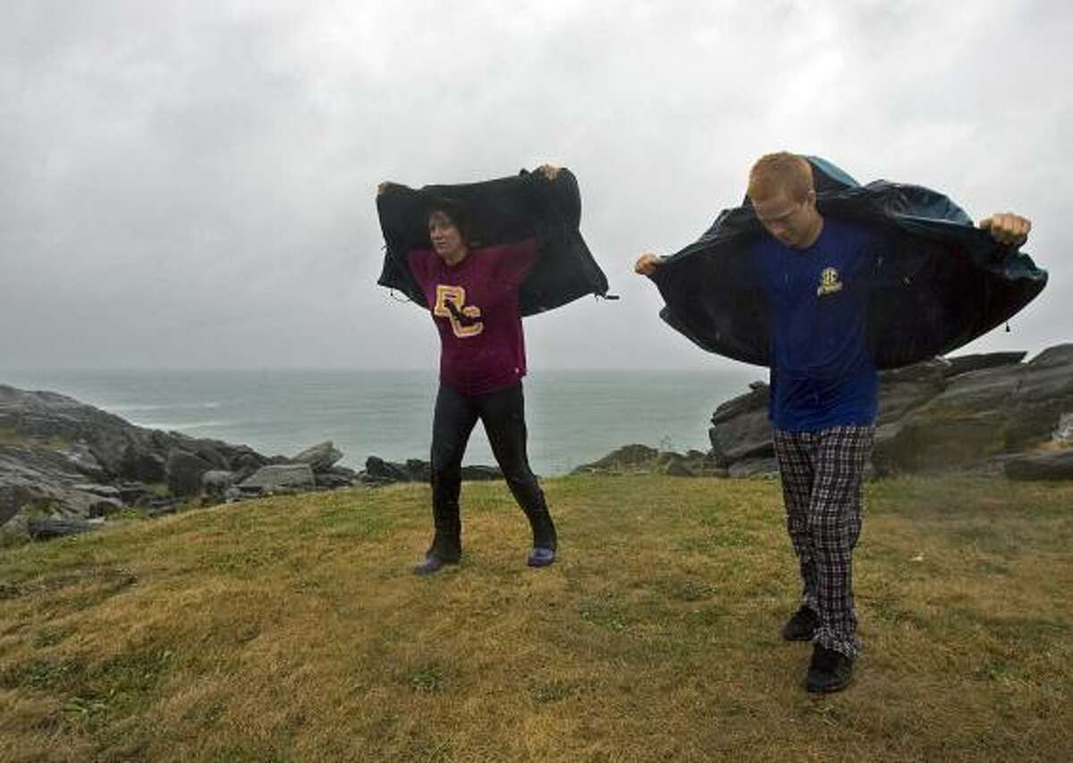Frances Robinson, left, and her son Jeremy Rotundo catch some wind as they brave Tropical Storm Earl on the rocks at Cape Forchu, Nova Scotia, Canada, on Saturday, Sept. 4, 2010. Heavy rain, high winds and pounding surf are battering the region.