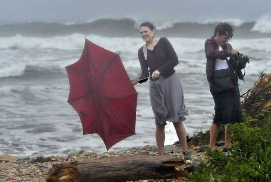 Meghan Walsh of Brooklyn, N.Y. battles the strong wind from Hurricane Earl to control her umbrella as her husband, Mike tries to protect his camera from the rain at Montauk Point Lighthouse on Friday, Sept. 3, 2010 in Montauk, N.Y. Photo: Kathy Kmonicek, AP