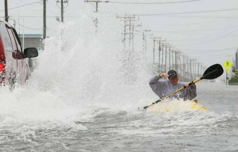 Kellie Maier gets splashed by a passing car while kayaking on water covered Highway 12, on September 3, 2010 in Kill Devil Hills, North Carolina. Hurricane Earl was downgraded to a category 2 before brushing the Outer Banks early Friday morning causing minimal damage. Photo: Mark Wilson, Getty Images