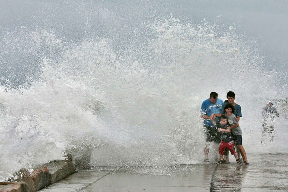 The Gallishaw family from Seekonk, Mass., braces for a large wave as it crashes over the Goosebury Island causeway in Westport, Mass., as Hurricane Earl approaches Friday, Sept. 3, 2010. Photo: Peter Pereira, AP