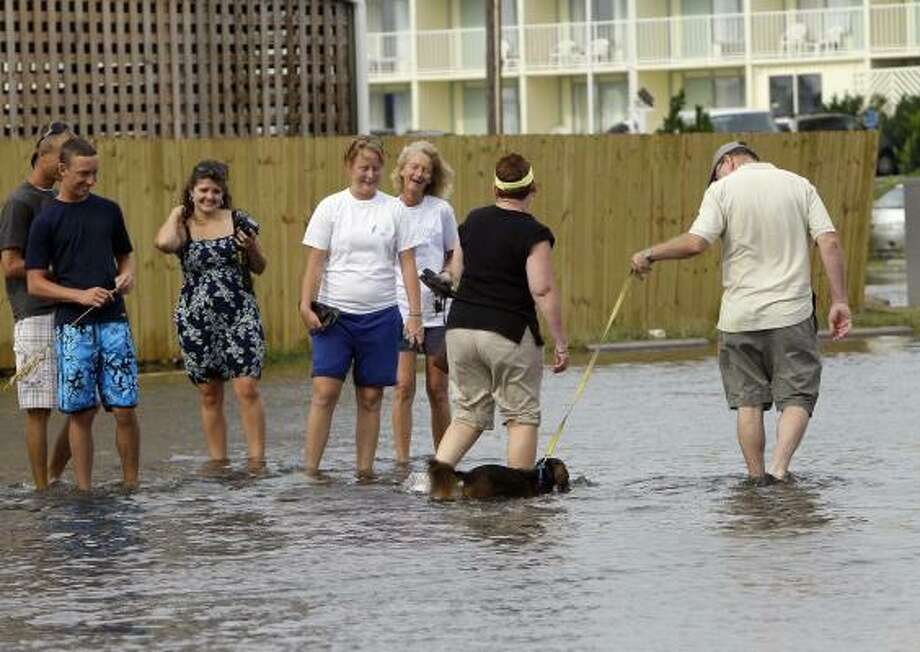 A couple walks a dog in standing water as others watch in Nags Head, N.C., Friday, Sept. 3, 2010, after Hurricane Earl dumped heavy wind and rain on North Carolina's Outer Banks. Photo: Gerry Broome, AP