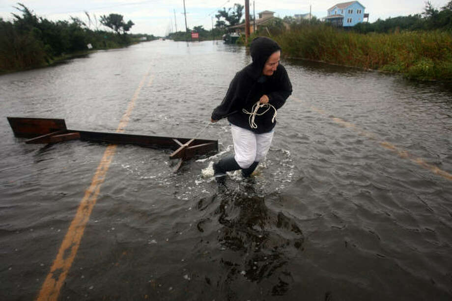 Kim Harper drags a workbench back to her home across flooded Hwy 12  in Frisco, N.C. Friday, Sept. 3, 2010 after sound side flood waters from Hurricane Earl carried it away overnight. Photo: Steve Early, AP