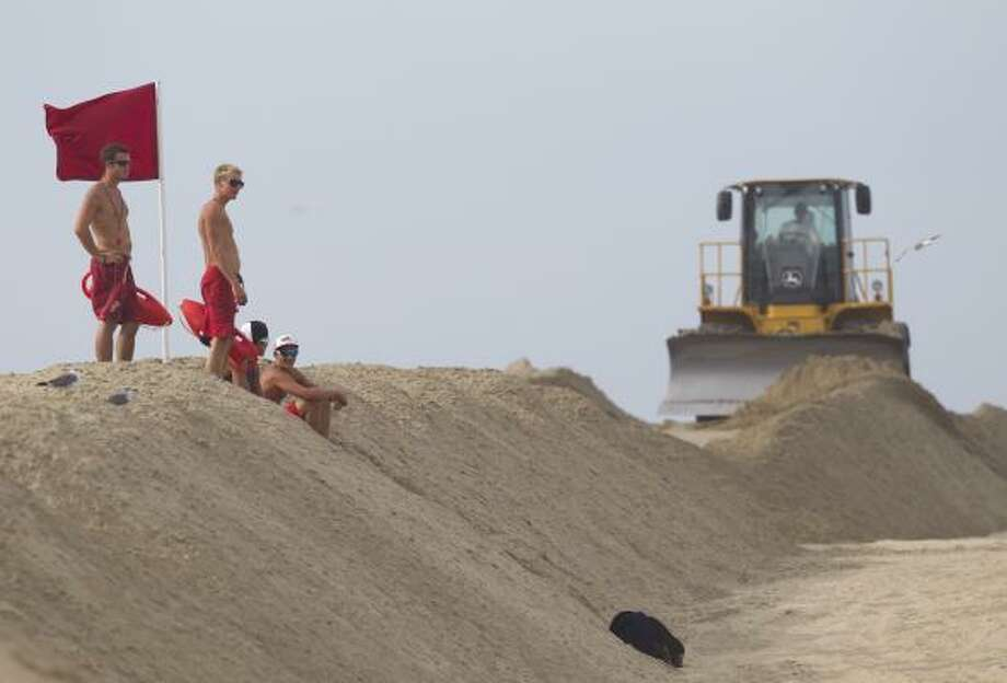 Virginia Beach lifeguards scan the water from the top of a protective sand berm that construction crews built to protect against storm surge from Hurricane Earl on Thursday, Sept.  2, 2010 in Virginia Beach, Va. Photo: Evan Vucci, AP