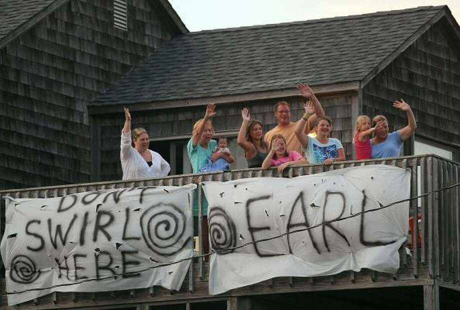 Members of the Wood and Rollins families from Newport News, Virginia stand on the balcony of their rented beach house waving at passing cars, on September 1, 2010 in Avon, North Carolina. The families say they will ride out the storm in their rented beach house. A hurricane watch has been issued for most of the North Carolina coastline due to the approaching Category 4 Hurricane Earl that is expected to pass the Outer Banks of North Carolina early on the morning of September 3. Photo: Mark Wilson, Getty Images