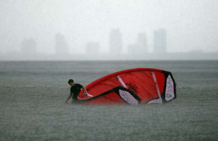 A kite surfer pulls the kite behind him in a heavy downpour as Hurricane Earl continues its track northward in the Caribbean on August 31, 2010 in Miami, Florida.  The system, a category 4 storm with maximum sustained winds at 135 mph, is projected to head towards the area of North Carolina and may stay strong northwards along the east coast of the United States. Photo: Joe Raedle, Getty Images