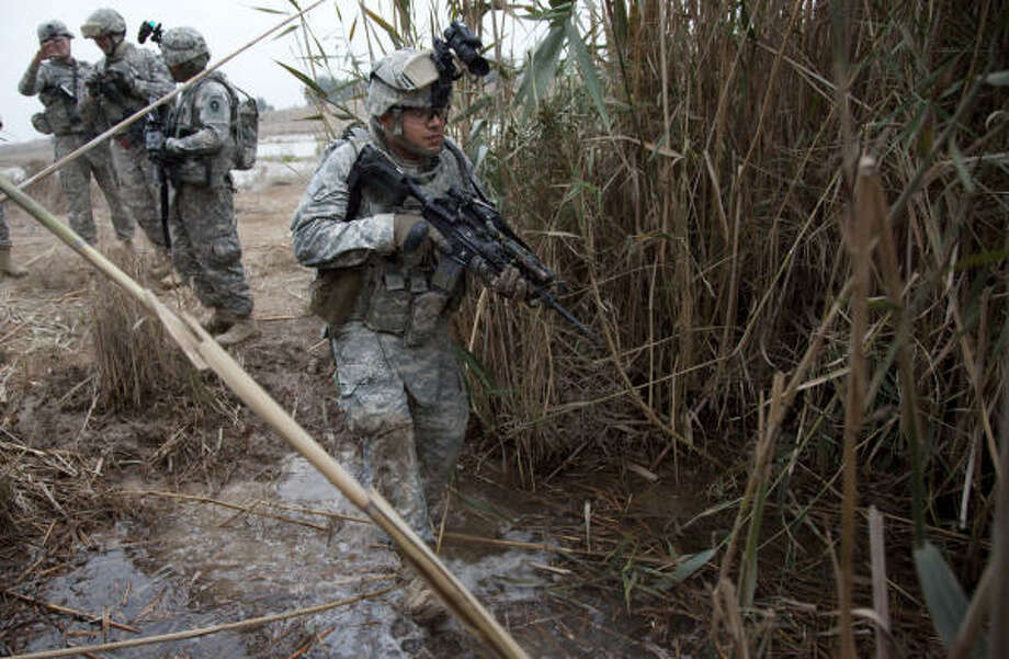 Spc. Ricardo Monreal, 22, of Pharr, crosses an irrigation ditch during a foot patrol last week in Baghdad, Iraq, while checking the perimeter of the Victory Base complex. Photo: Mayra Beltran, Chronicle
