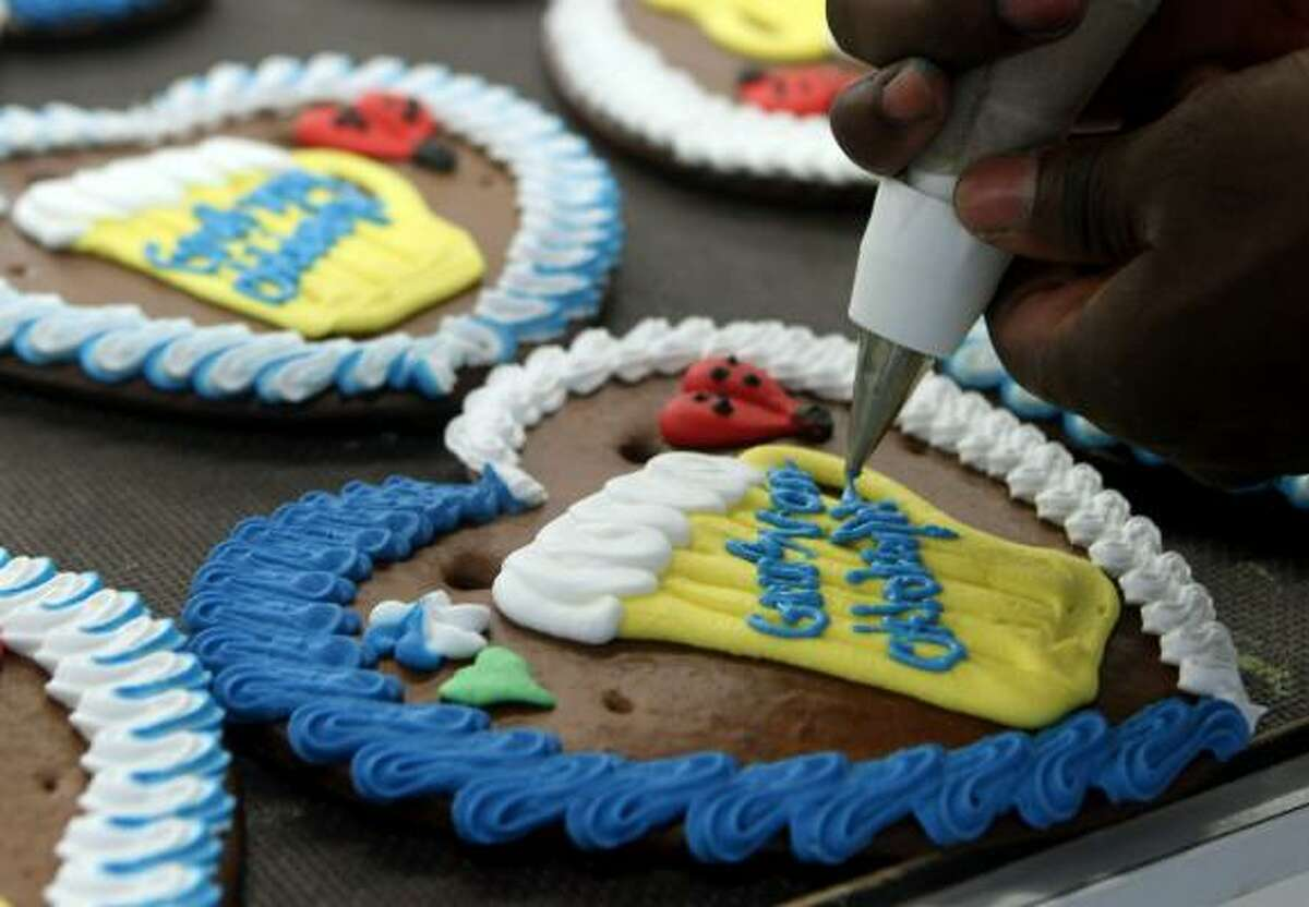 An employee finishes the sugar icing decoration on gingerbread hearts to be sold at the Oktoberfest celebration in Aschheim near Munich, Germany.