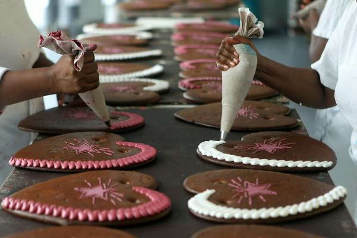 Employees paint the sugar icing decoration on gingerbread hearts.