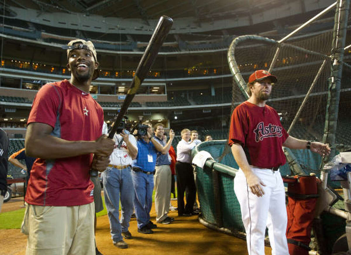 Rockets guard Aaron Brooks picks up a bat while standing next to Astros hitting coach Jeff Bagwell.
