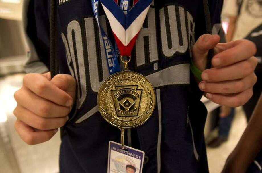 Pearland Little Leaguer, Hunter Smith, 12, wears a Little League World Series medal at the baggage claim. Photo: Johnny Hanson, Chronicle