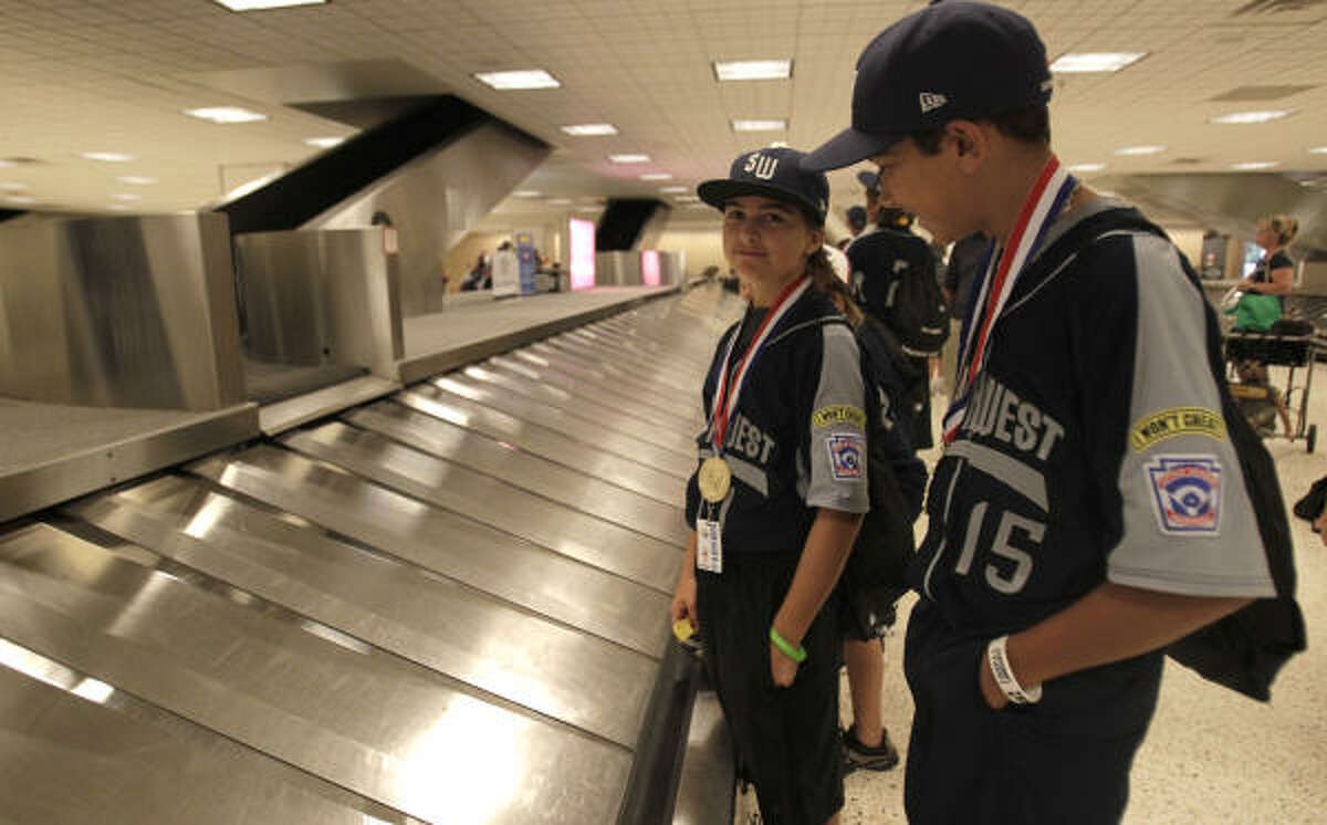 Pearland Little League's Jorge Gutierrez, right, and Pryce Beshoory wait for their luggage in baggage claim after they returned home to Houston.