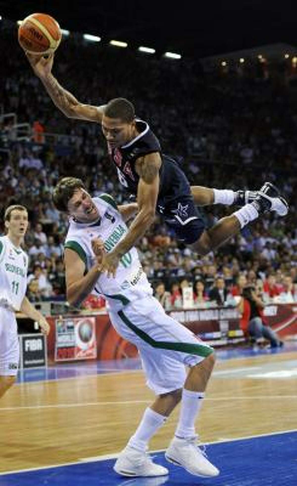 USA's Andre Iguodala, right, falls over Slovenia's Bostjan Nachbar as he goes up to the basket.