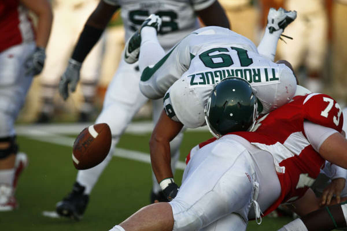 Stratford's Tim Rodriguez (19) forces a fumble during the first quarter of a game against Memorial.