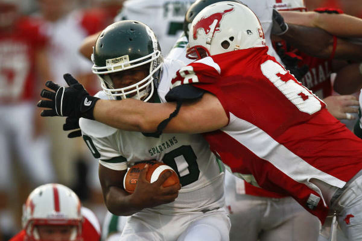 Stratford's Terrence Louis (10) runs with the ball as Memorial's Leighton Gilbert (68) makes the tackle.