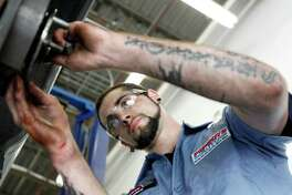 In this July 6, 2011 photo, technician Chris Shannon works on a costumers car at a Pep Boys Auto retail and service location, in Philadelphia. The U.S. service sector, which employs nearly 90 percent of the country?s work force, expanded for a 20th straight month in July, though at a slower pace than in June. (AP Photo/Matt Rourke)