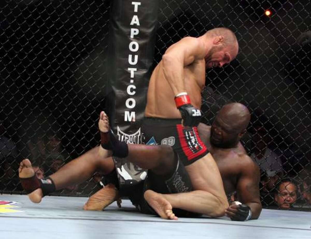 Randy Couture pins James Toney against the cage and prepares to land a strike with the right.