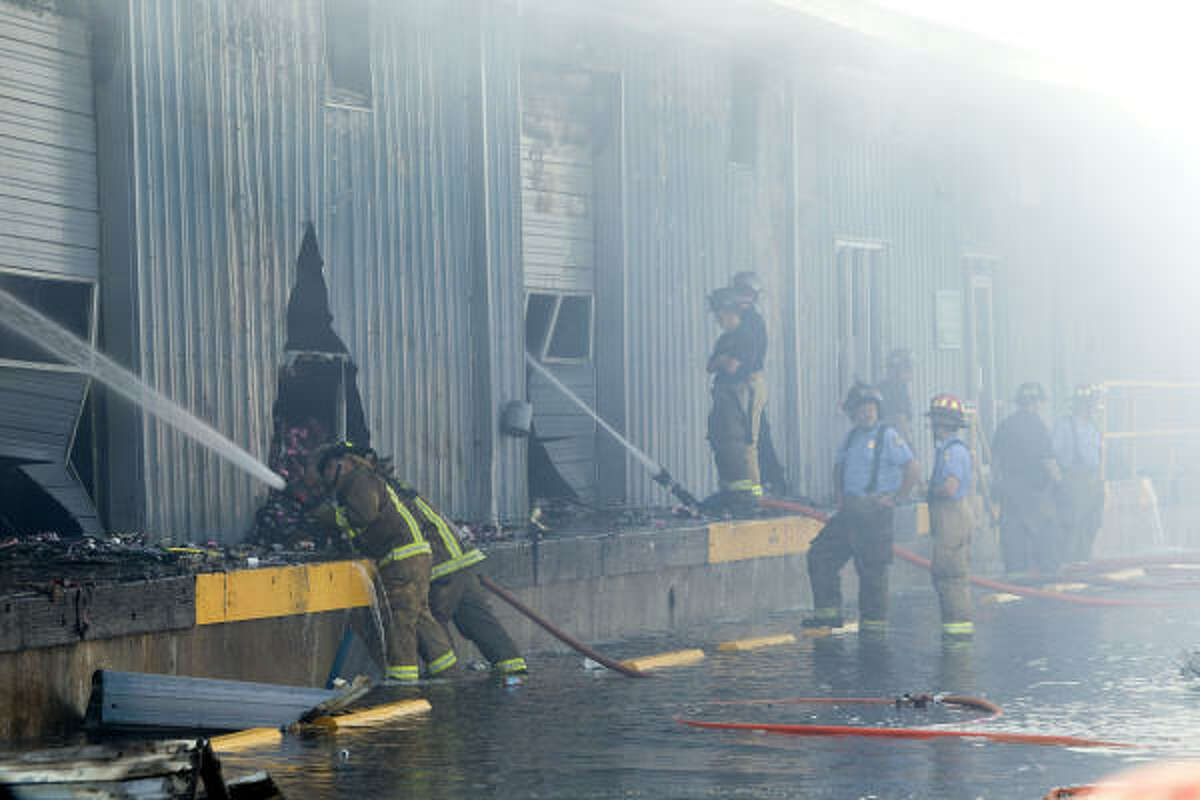 Houston firefighters pour water on the smoldering shell of a warehouse that caught fire in the early Friday morning. Harris County voting machines were destroyed about two months before early voting in a 3-alarm fire at a warehouse in north Houston.