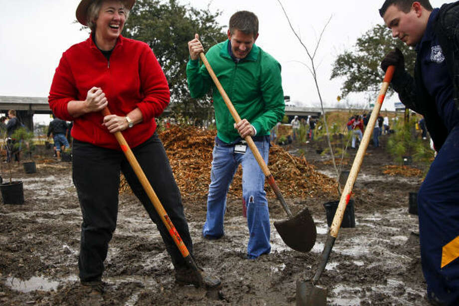 Mayor Annise Parker laughs about the muddy conditions as she helps volunteers Dan Pederson, center, and Alex Soliz during the planting of nearly 1,500 trees on an esplanade at North Wayside and Interstate 10 in an Arbor Day project on Saturday. Photo: Michael Paulsen, Chronicle