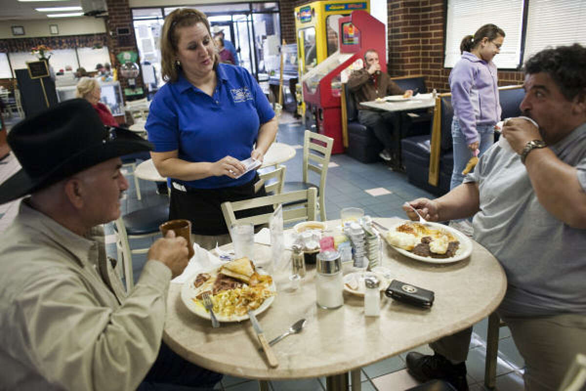 Server Taffanie Stavely talks with Robert Rangel, left, and George Peña at Tony's Family Restaurant, one of the businesses in Sealy that depend — directly or indirectly — on BAE. The loss of a major contract likely means unemployment for many or all of the plant's 3,200 workers.