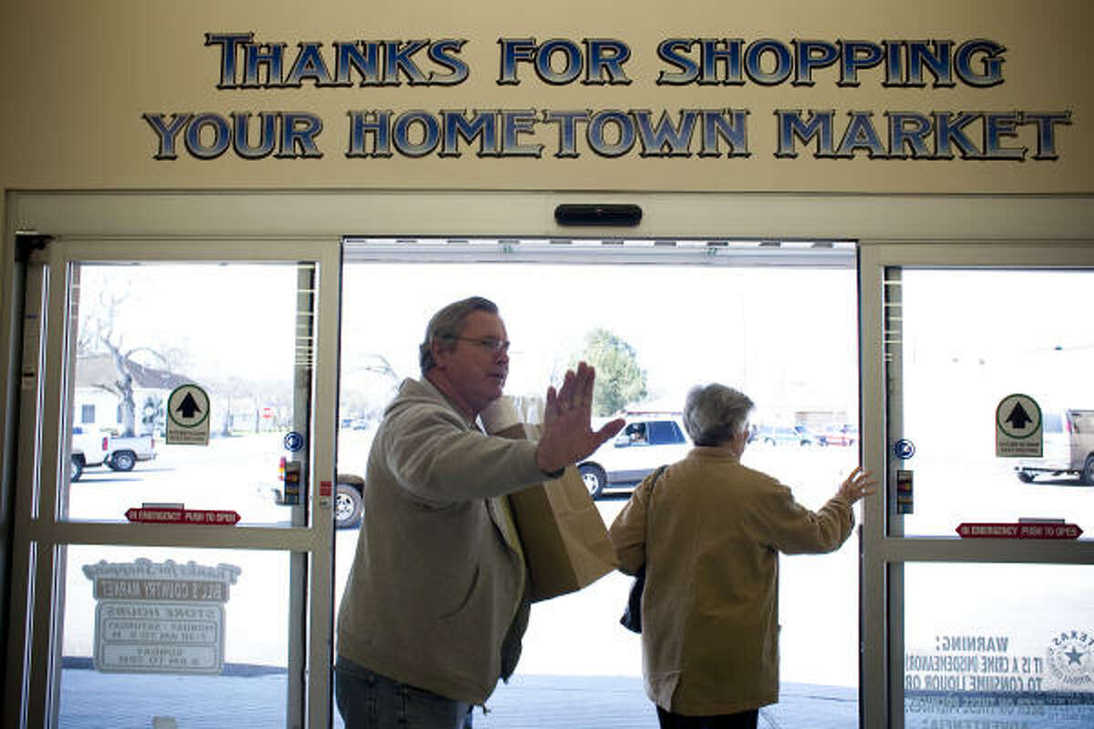 Sealy residents Dane Rudloff and his mother, Frances Rudloff, wave to Kevin Krampitz, owner of Bill's Country Market, a business owner confronting the BAE setback.
