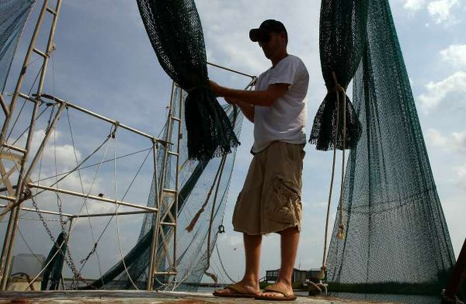 Daniel May sets up his nets on a shrimping barge located in a bayou on Aug. 16, 2010 near DuLarge, L