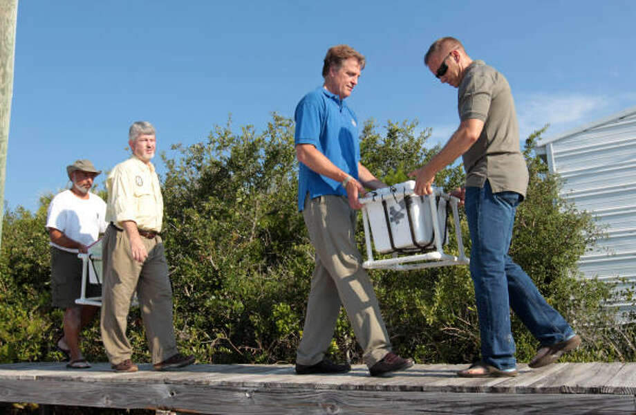 Jeff Trandahl, right, executive director of the National Fish and Wildlife Foundation, and Thomas Strickland of the U.S. Dept. of the Interior, second from right, carry a cooler full of sea turtle eggs after harvesting them from the sand in Port St. Joe, Fla.,  on Friday, July 9, 2010. Photo: Dave Martin, AP