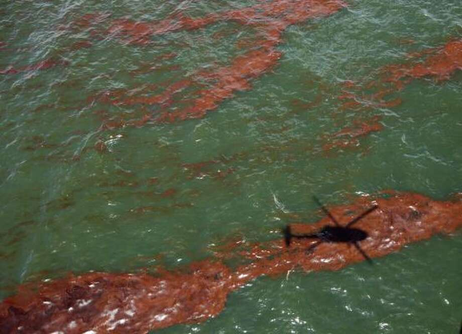 The shadow of a helicopter passes over oil from the Deepwater Horizon oil spill in waters less than 10 miles off the coast of Grand Isle, La.,  Monday, June 28, 2010. Photo: Gregory Bull, AP