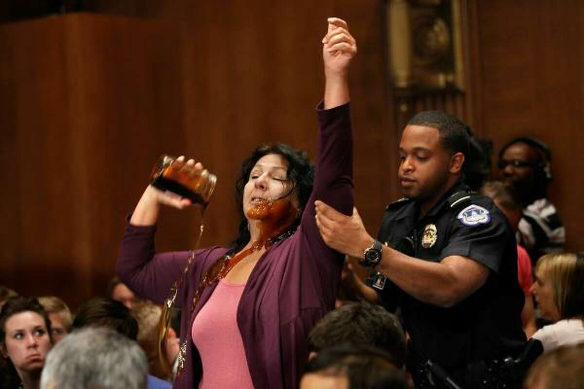 Commercial fisherwoman Diane Wilson, of Seadrift, Texas, pours a jar of syrup made to look like oil over herself as a police officer drags her from a Senate committee hearing on June 9, 2010 about the BP Deepwater Horizon oil spill.