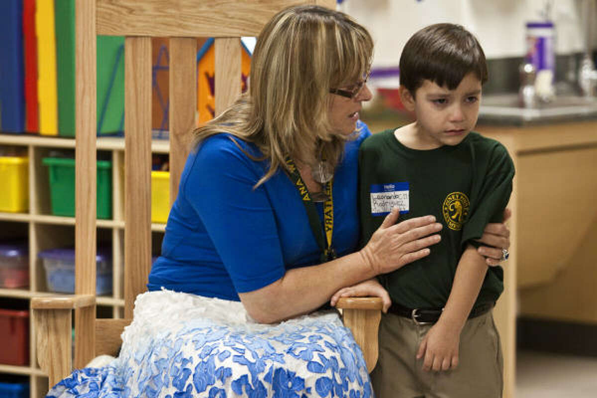 Ana Withoff helps comfort new kindergarten student Leonardo Rodriguez, 5, during the first day of school at Piney Point Elementary.
