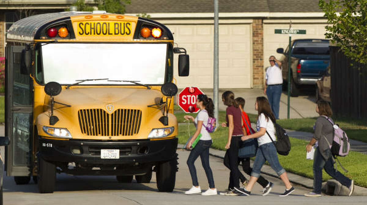 Students walk across the street to board a bus bound for York Junior High on the first day of school in the Conroe Independent School District.