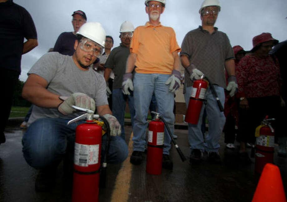 Ben Avner (al frente) y Donald Sexton (camiseta anaranjada) preparan sus extinguidores como parte de una sesión de capacitación de vecinos ofrecida por CERT en el Centro Cristiano West Houston. Una de las habilidades aprendidas en la sesión es la de cómo controlar pequeños incendios. Photo: Karen Warren, La Voz