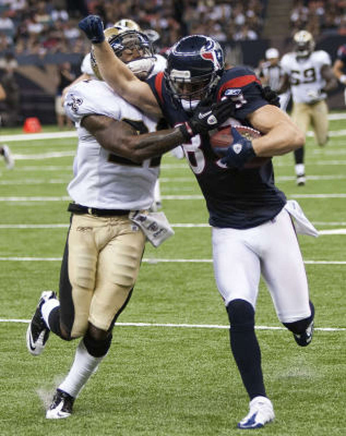 Texans receiver David Anderson tries to fight off Saints safety Chip Vaughn after making a catch during the third quarter. Anderson had three catches for 61 yards.
