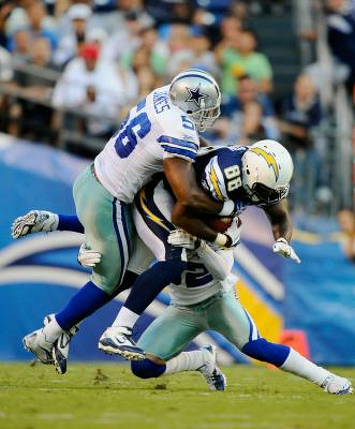Chargers fullback Kris Wilson is tackled by Cowboys linebacker Bradie James after catching a pass.