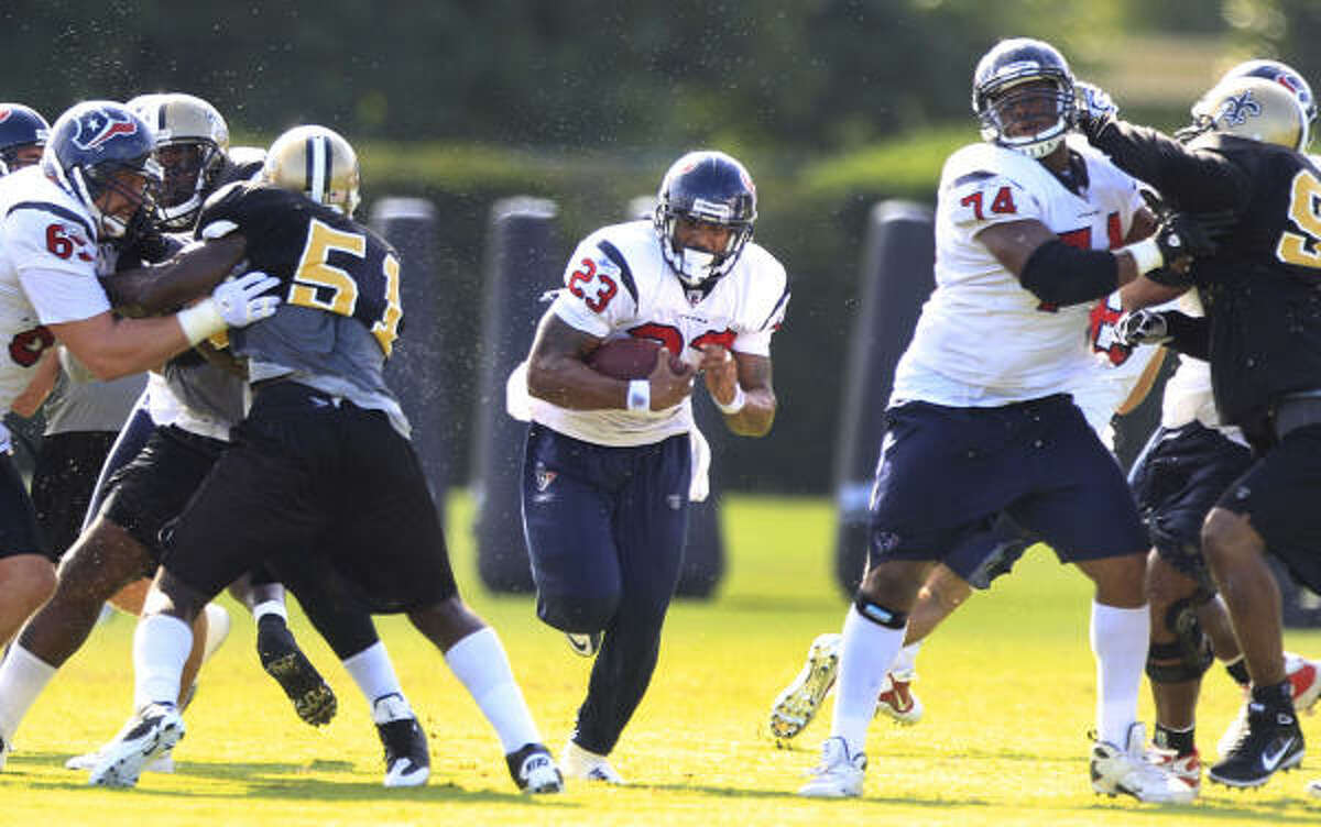 Texans running back Arian Foster runs through a hole in the line during a combined practice against the New Orleans Saints on Thursday in Metairie, La.