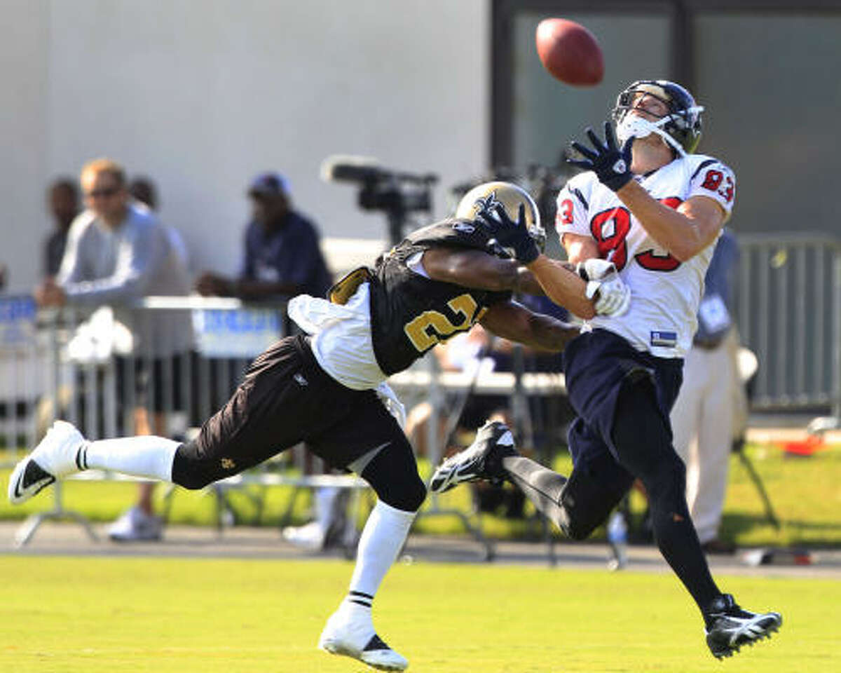Texans wide receiver Kevin Walter runs under a pass while being defended by Saints cornerback Tracy Porter.