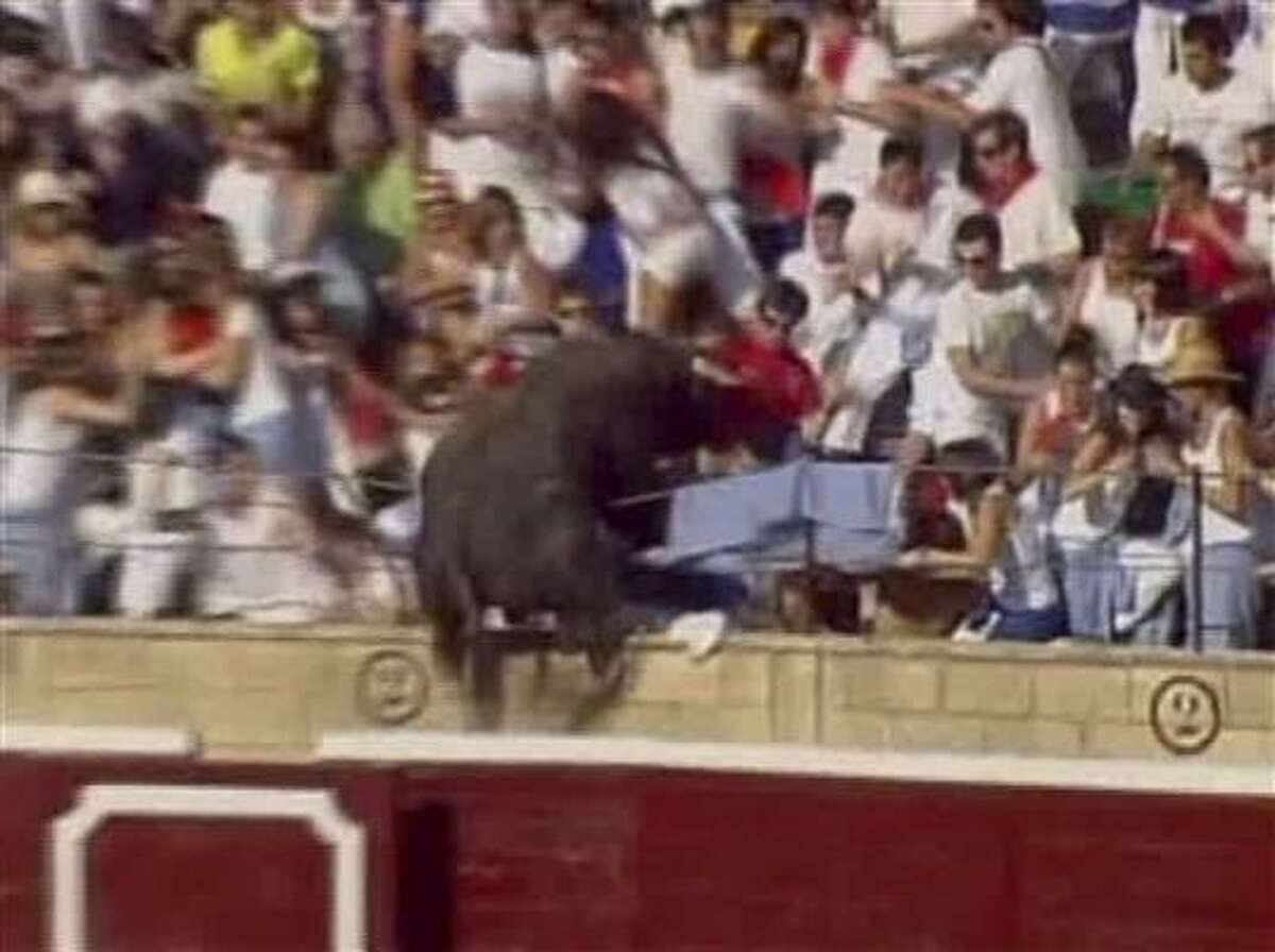 In this TV image provided by ETB via APTN a holds the bull by the tail after it jumped 10 meters from the ring into the stands at the Tafalla bullring in Spain causing panic as it lurched through the screaming crowd, charging and tossing everything he could.
