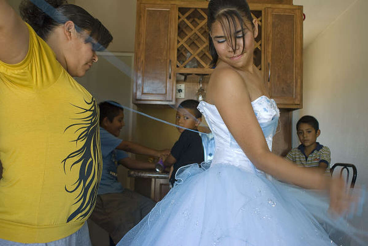 A quiceañera is a rite-of-passage ritual for many 15 year-old girls in Latin American countries, similar to a 'sweet sixteen' or debutante coming-out party in the US. Paloma Lozoya is one of the girls selected for the quinceannera by the city. Paloma gets into her gown for the celebration with some help from her mother, Erika Contreras.