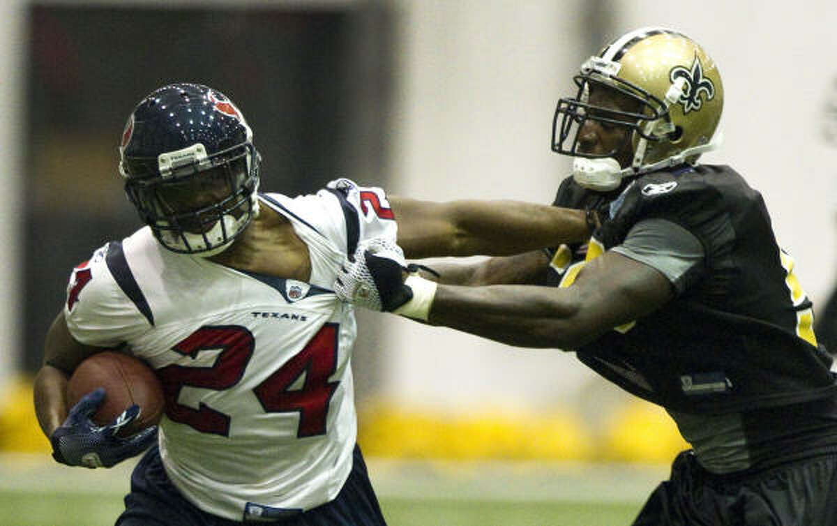 Texans running back Jeremiah Johnson tries to pull away from Saints linebacker Anthony Waters.