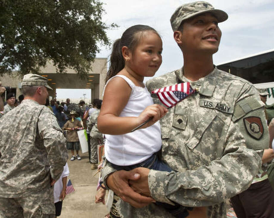 Spc. Armando Derrickson holds his four-year-old daughter Lanae Derrickson upon his return home after a one-year deployment in Afghanistan with the U.S. Army Reserve's 453rd Inland Cargo Transfer Company. Photo: James Nielsen, Chronicle