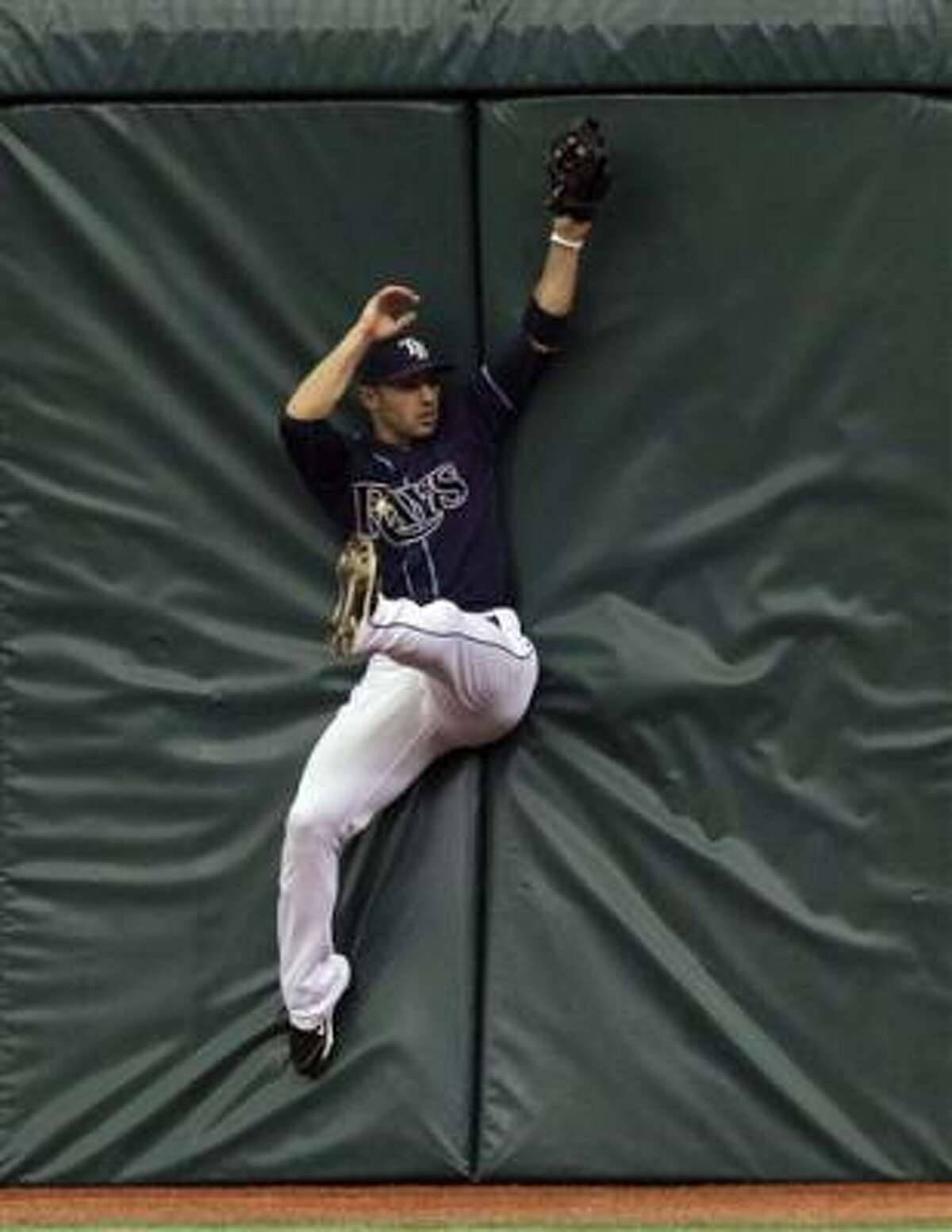 Tampa Bay Rays right fielder Sean Rodriguez crashes into the wall after robbing Texas Rangers' Julio Borbon of an extra base hit Wednesday, Aug. 18 in St. Petersburg, Fla.