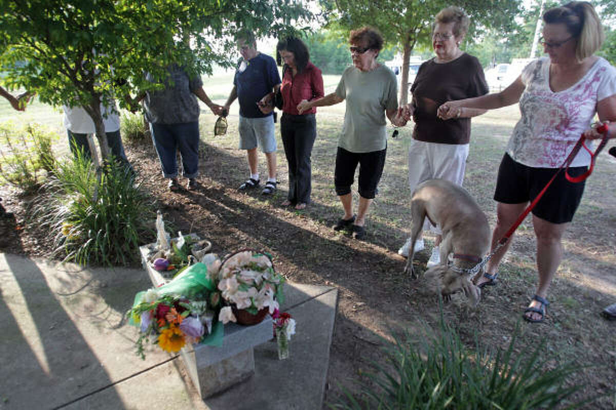 The community says a prayer at the memorial site for Jennifer Ertman and Elizabeth Pena.