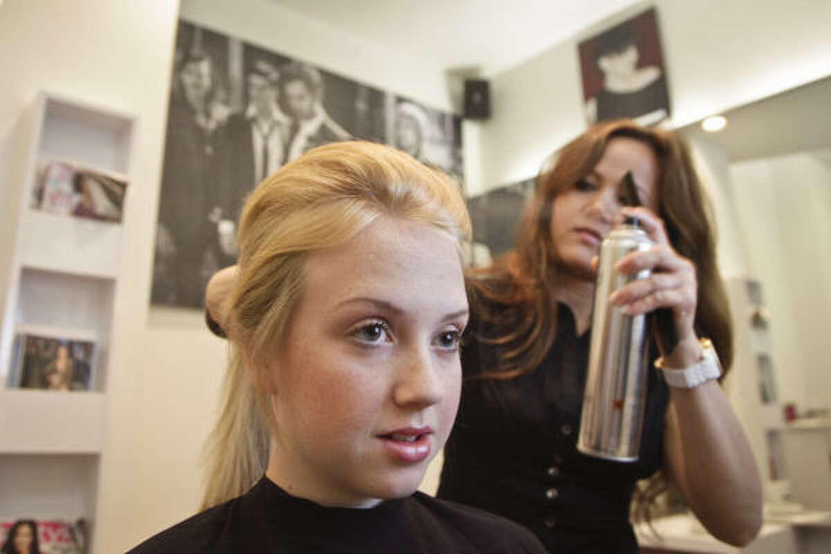 Using a teasing comb, tease each of the three sections, spraying each lightly with quick-drying (aerosol) hairspray.