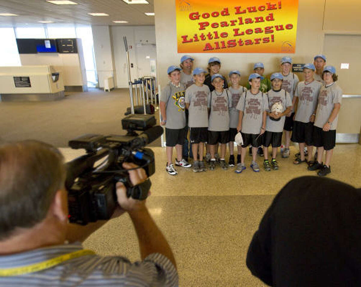 Members of the Pearland Little League team get their photo taken in front of a banner at their gate at Houston Intercontinental Airport on Tuesday as they prepare to leave for South Williamsport, Pa., and the Little League World Series.