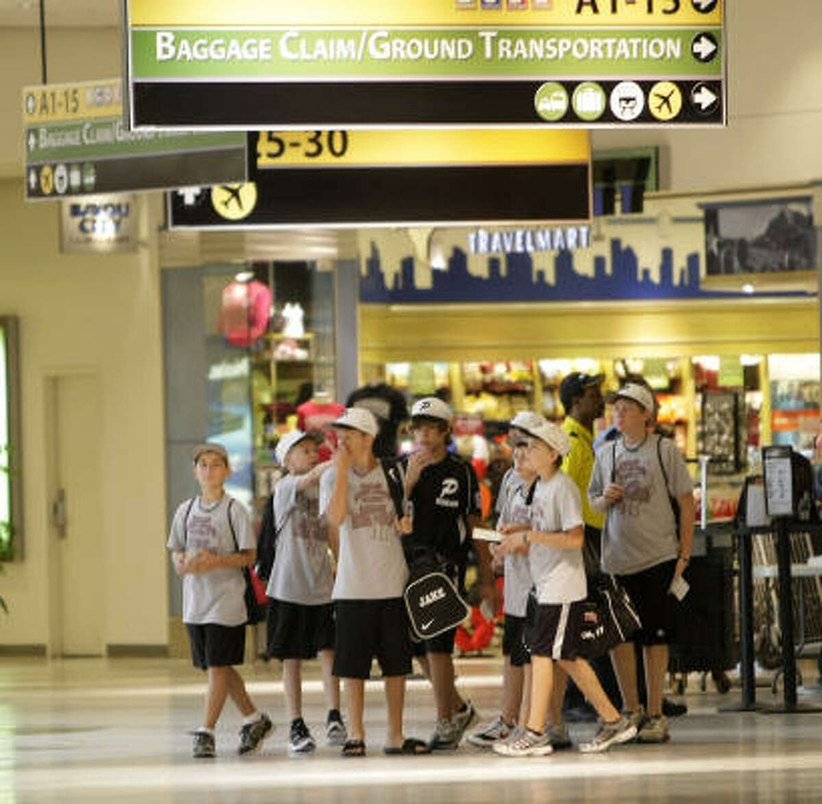 Pearland Little Leaguers walk through the terminal.