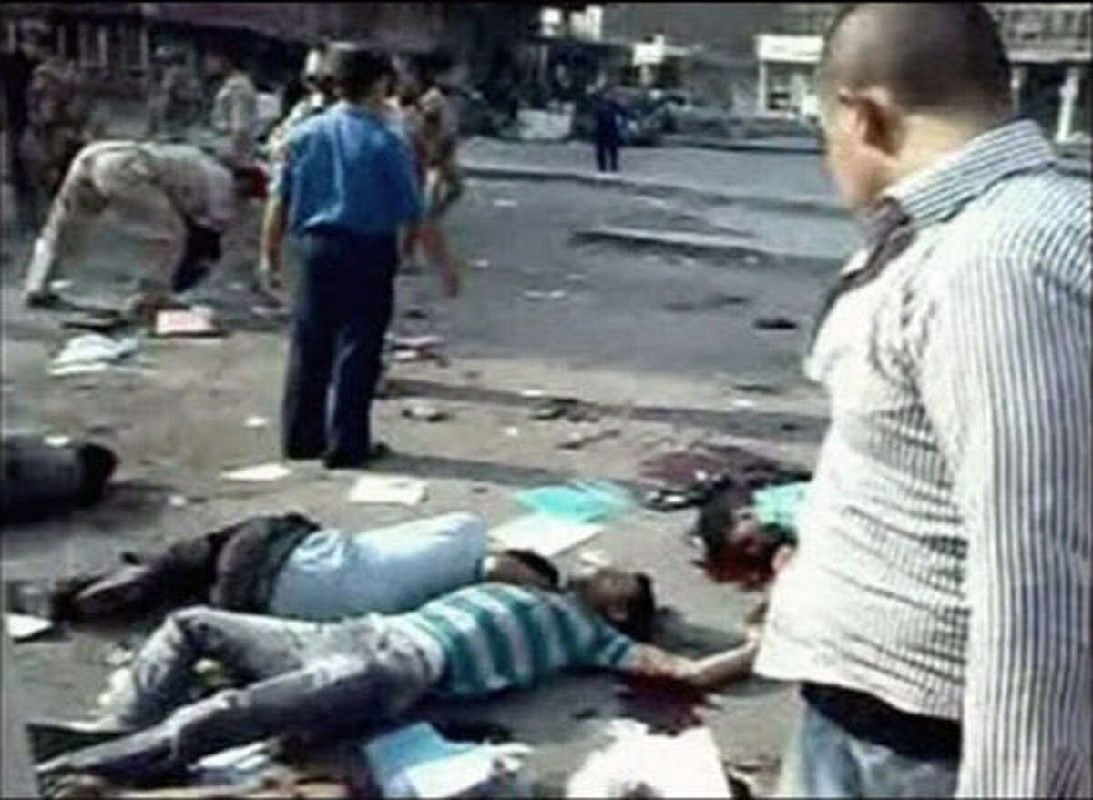 In this image from mobile phone video people look on the scene where at least 60 people were killed and 125 wounded in Iraq on Tuesday Aug 17 2010 when a suicide bomber blew himself up among hundreds of army recruits who had gathered near a military headquarters in the capital, Baghdad.